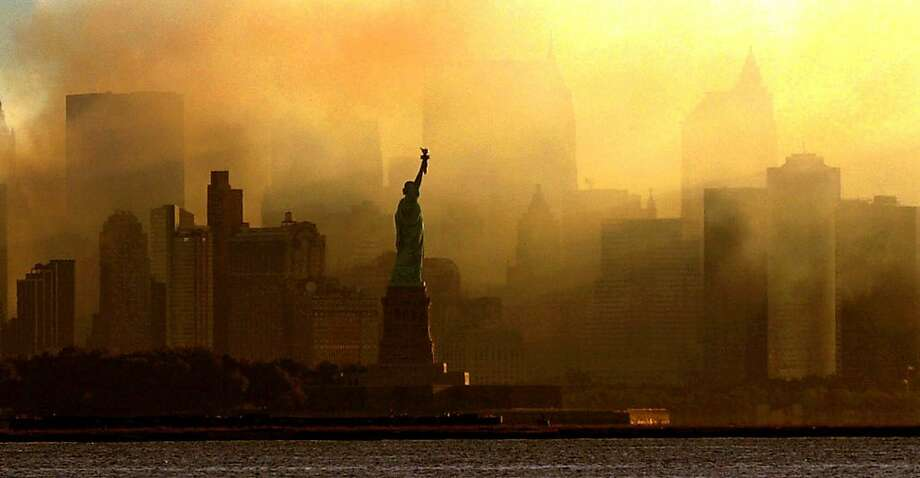The Statue of Liberty is seen at first light in this view from Jersey City, N.J., against a smoke-filled backdrop of the lower Manhattan skyline, early Saturday, Sept. 15, 2001.  Photo: Dan Loh, AP