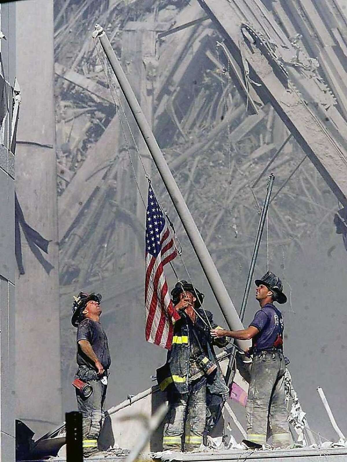 Brooklyn firefighters George Johnson, left, of ladder 157, Dan McWilliams, center, of ladder 157, and Billy Eisengrein, right, of Rescue 2, raise a flag at the World Trade Center in New York, in this Sept. 11, 2001, file photo, as work at the site continues after hijackers crashed two airliners into the center. In the most devastating terrorist onslaught ever waged against the United States, knife-wielding hijackers crashed two airliners into the World Trade Center, toppling its twin 110-story towers. This year will mark the fifth anniversary of the attacks. (AP Photo/ Copyright 2001 The Record (Bergen County, NJ), Thomas E. Franklin, Staff Photographer/FILE) MANDATORY CREDIT NO SALES ONLINE OUT