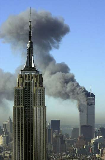Plumes of smoke rise from the World Trade Center in New York. The Empire State Building is seen in t