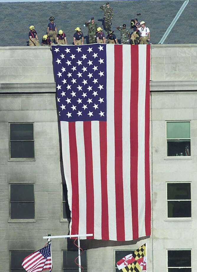 Firefighters unfurl an American flag from the roof of the Pentagon Wednesday, Sept. 12, 2001, as President Bush visits the area of the Pentagon where an airliner, hijacked by terrorists, crashed into the building. Photo: Ron Edmonds, AP