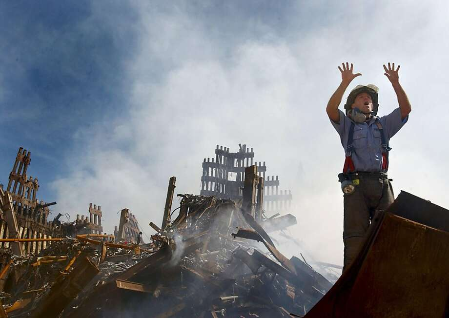 A New York City fireman calls for 10 more rescue workers to make their way into the rubble of the World Trade Center on Sept. 14, 2001.  Photo: Jim Watson
