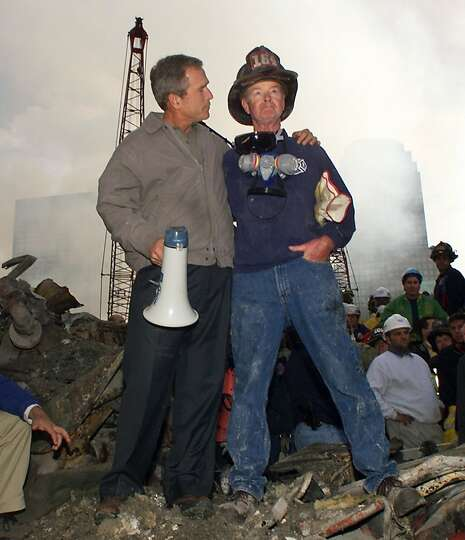 President George W. Bush embraces firefighter Bob Beckwith while standing in front of the collapse