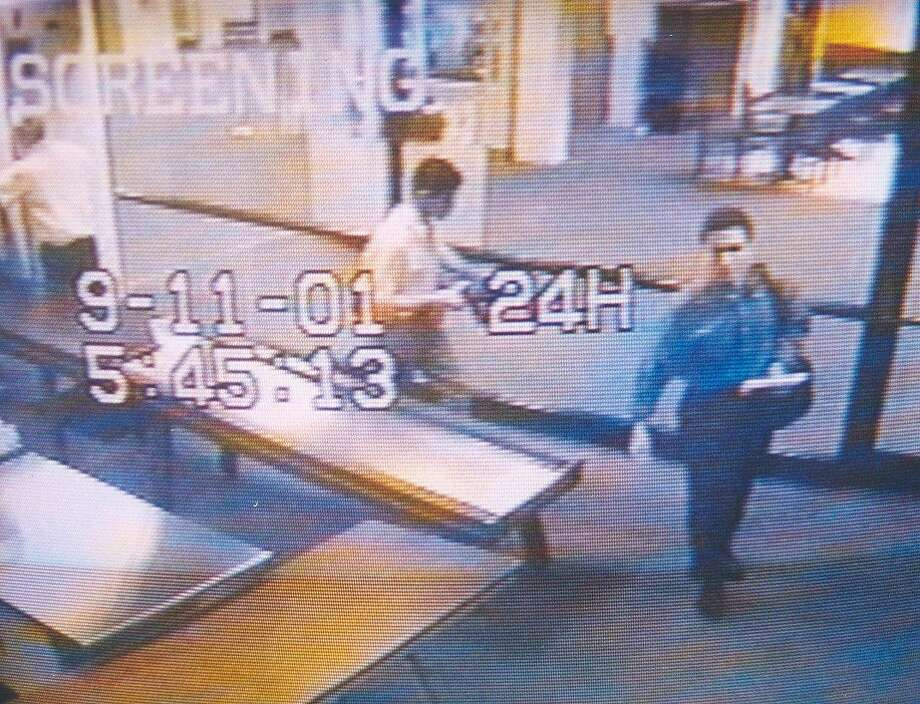 A surveillance camera photographs suspected hijackers Mohammed Atta (R) and Abdulaziz Alomari (C) as they pass through airport security Sept. 11, 2001, at Portland International Jetport In Maine. Authorities say the two men took a commuter flight to Boston before boarding American Airlines Flight 11, one of the two jets that were crashed into the World Trade Center. Photo: U.S. Navy