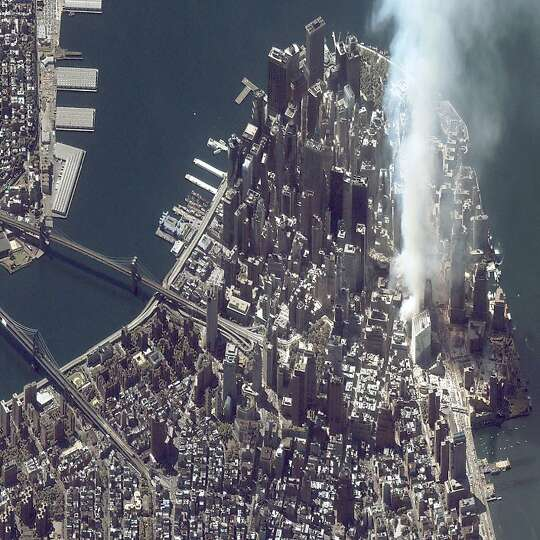 A satellite image of lower Manhattan shows smoke and ash rising from the site of the World Trade Cen