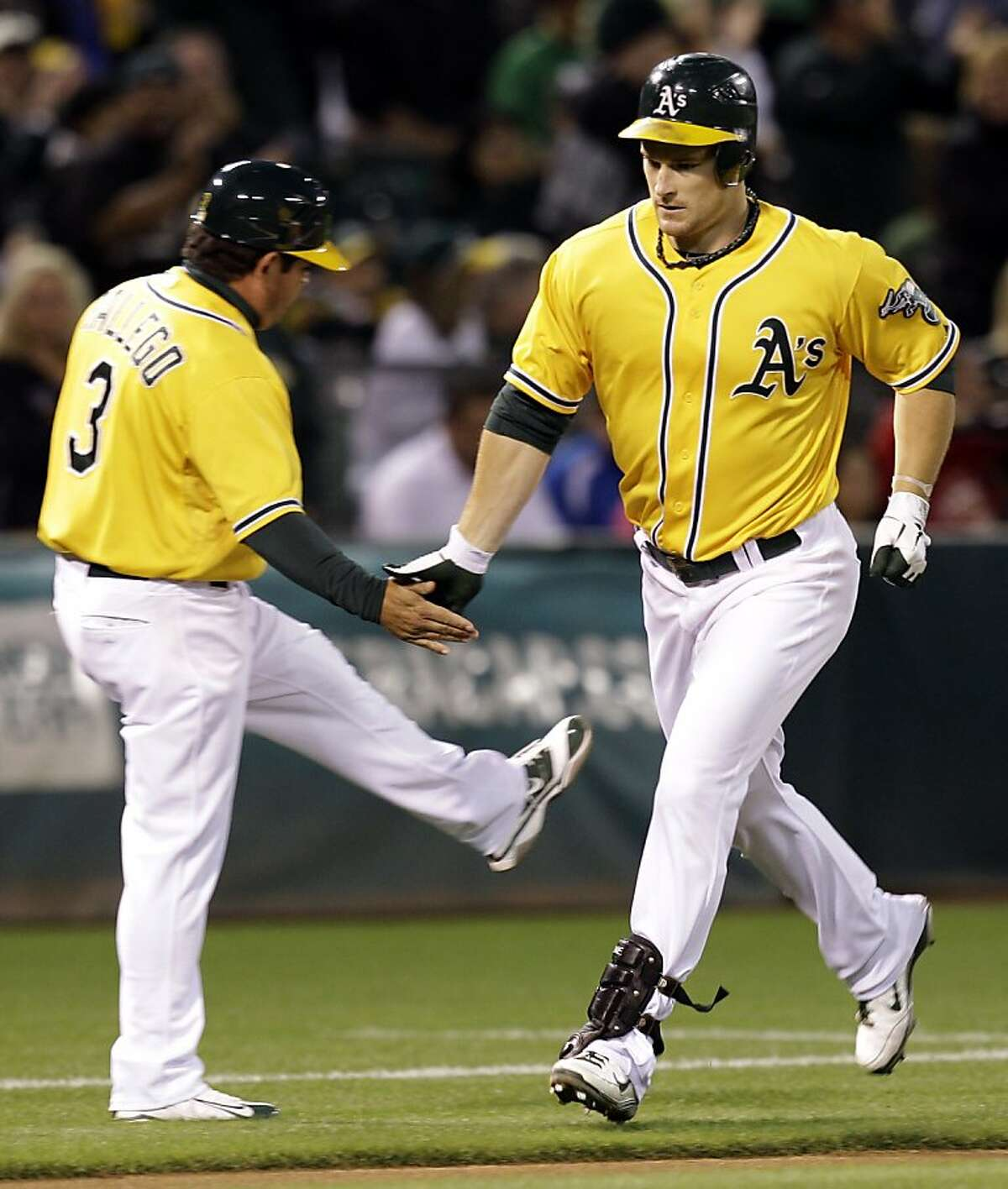 Oakland Athletics' Josh Willingham, right, is congratulated by third base coach Mike Gallego after hitting a home run off Detroit Tigers' Doug Fister during the second inning of a baseball game on Friday, Sept. 16, 2011, in Oakland, Calif. (AP Photo/Ben Margot)
