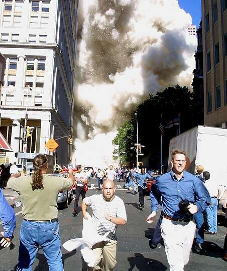 Pedestrians run from the scene as one of the World Trade Center Towers collapses.