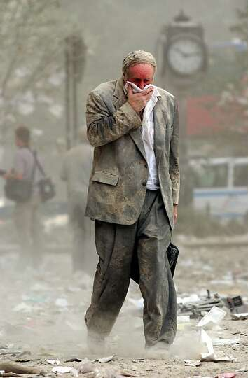 Edward Fine covers his mouth as he walks through the debris after the collapse of one of the World T