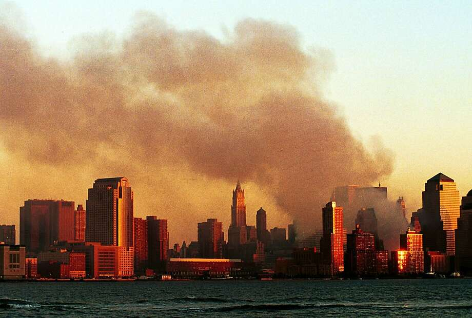 Smoke pours from the World Trade Center in Manhattan Sept. 12, 2001 from a vantage point in Hoboken, N.J.  Photo: Chris Hondros