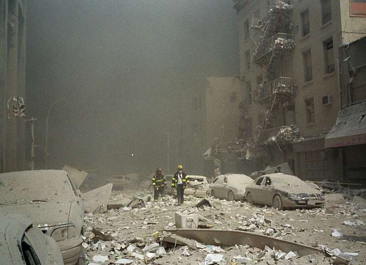 Firemen walk through a dust and debris covered street in lower Manhattan on Sept. 11, 2001.