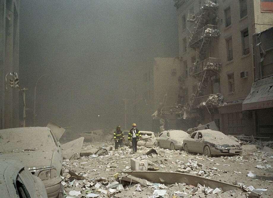 Firemen walk through a dust and debris covered street in lower Manhattan on Sept. 11, 2001.  Photo: Richard Cohen, AP