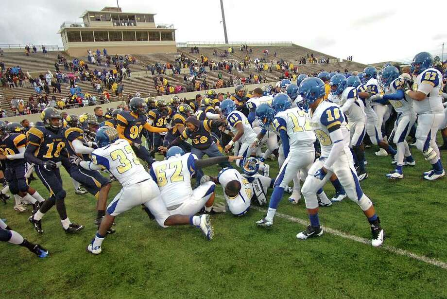 Ozen and La Marque players collide in a brawl shortly after shaking hands at the end of a game at Stallworth Stadium on Saturday. Security officials used pepper spray to break up the melee which  followed a smaller scuffle occurring in the fourth quarter.  Photo taken Saturday, November 26, 2011 Guiseppe Barranco/The Enterprise Photo: Guiseppe Barranco, STAFF PHOTOGRAPHER / The Beaumont Enterprise