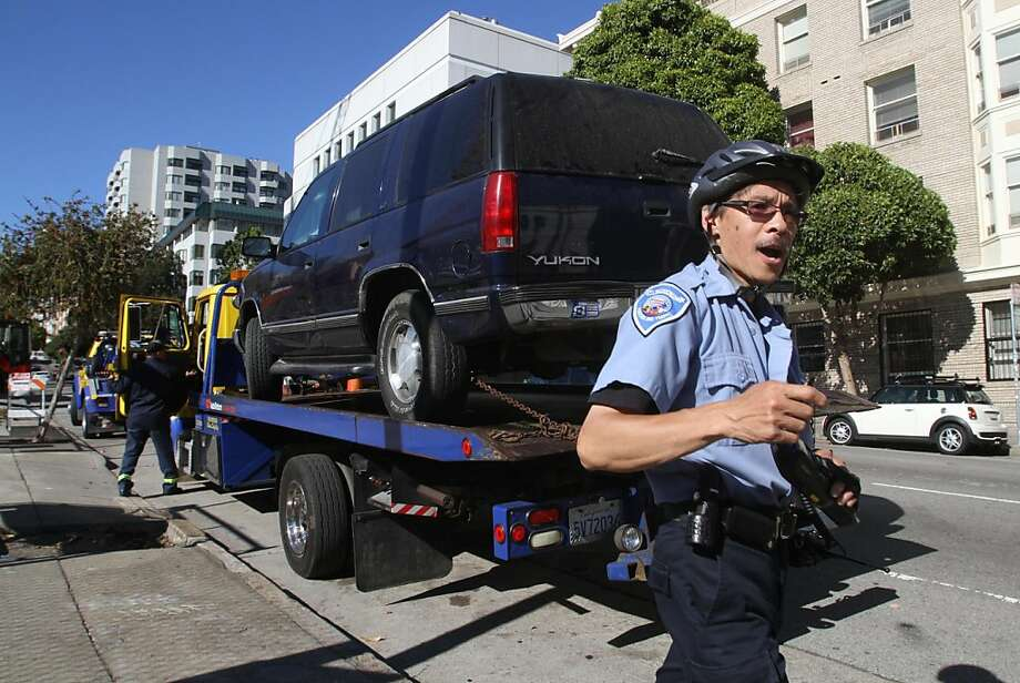 A parking enforcement officer walks to his vehicle after ticketing a car that is being towed on Franklin St. on Tuesday, Sept. 20. Board of Supervisors President David Chiu is proposing a new program that will alert drivers to upcoming tows via text, emails, or robocalls. Photo: Mathew Sumner, Special To The Chronicle