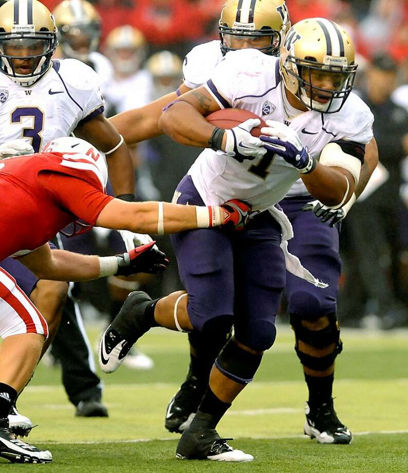 Washington's Chris Polk (1) gets by Nebraska's Austin Cassidy (8) during their  NCAA college football game, Saturday, Sept 17, 2011, in Lincoln, Neb. Nebraska beat Washington 51-38. (AP Photo/Dave Weaver) Photo: Dave Weaver, AP