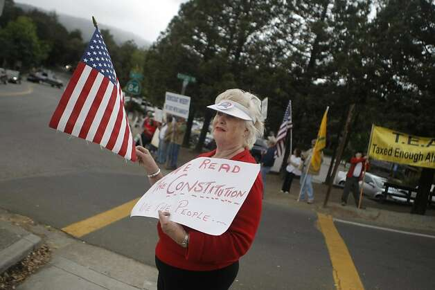 A Tea Party activist waves a flag during a protest in Woodside, Calif., on Sunday, Sept. 25, 2011.  The President is in the area doing a fundraiser. Photo: Dylan Entelis, The Chronicle