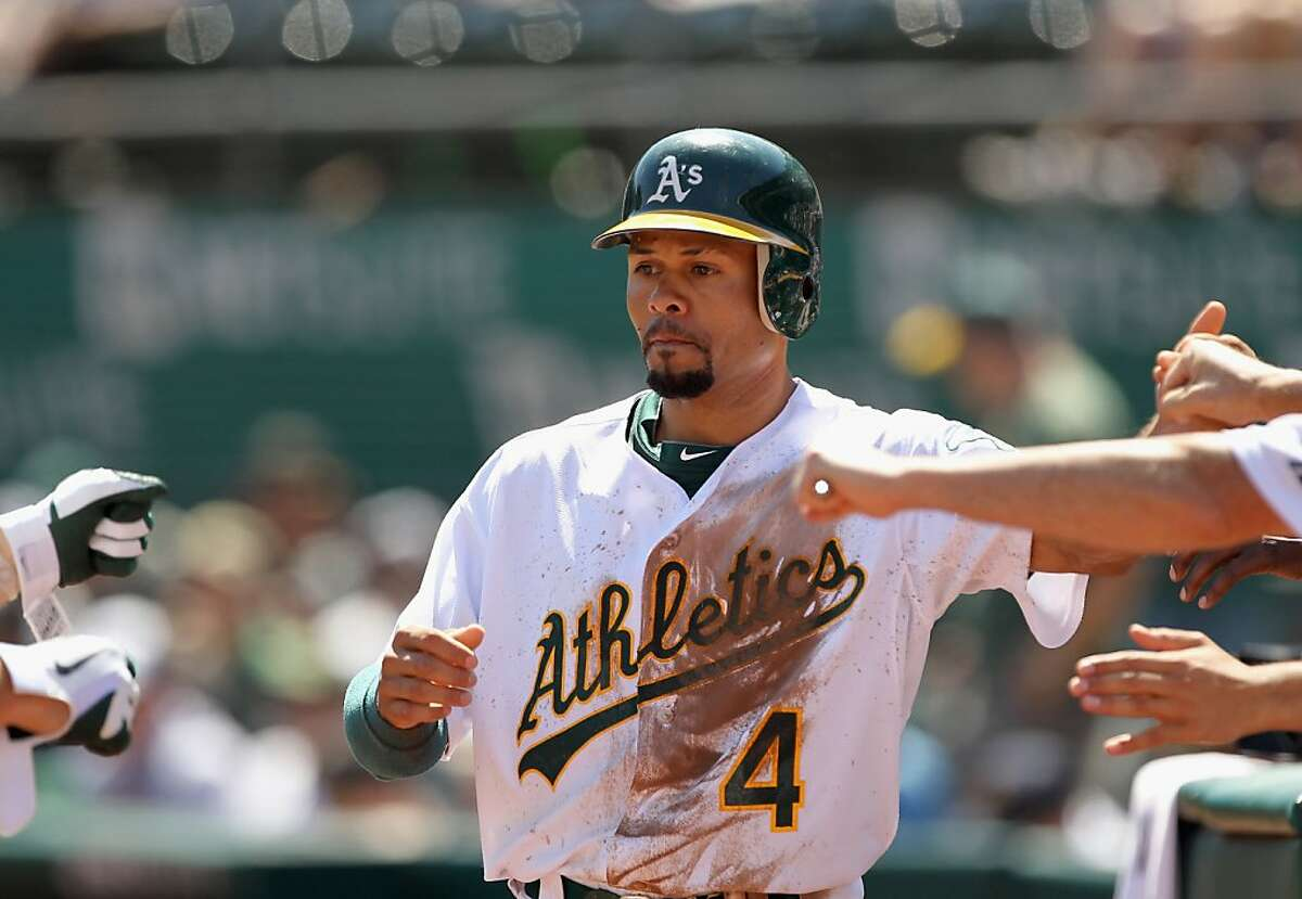 OAKLAND, CA - SEPTEMBER 07: Coco Crisp #4 of the Oakland Athletics is congratulated by teammates after he scored in the first inning of their game against the Kansas City Royals at O.co Coliseum on September 7, 2011 in Oakland, California. (Photo by Ezra Shaw/Getty Images)