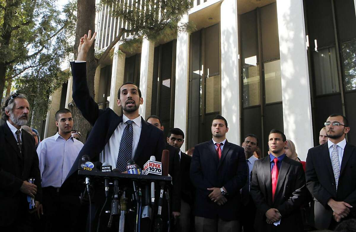 Student Mohamad Abdelgany, at podium, raises his hand as his fellow students and other supporters take questions from the media after being convicted in Santa Ana, Calif., Friday, Sept. 23, 2011. A California jury on Friday convicted 10 Muslim students of illegally disrupting a speech by Israeli Ambassador Michael Oren at the University of California, Irvine, last year, including Abdelgany, in a case that has stoked an intense debate about free speech. (AP Photo/Damian Dovarganes)