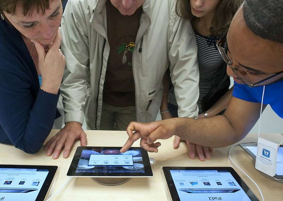 An Apple Inc. employee, right, demonstrates an iPad 2 to customers during the opening of the company's new store in Le Chesnay, near Paris, France, on Saturday, Sept. 24, 2011. Apple Inc. is cutting orders to vendors in the supply chain for its iPad tablet computer, a move that may result in slower sales for companies including Hon Hai Precision Industry Co., JPMorgan Chase & Co. said in a report. Photographer: Fabrice Dimier/Bloomberg  Ran on: 09-27-2011 Photo caption Dummy text goes here. Dummy text goes here. Dummy text goes here. Dummy text goes here. Dummy text goes here. Dummy text goes here. Dummy text goes here. Dummy text goes here.###Photo: bb27_briefing_applePH1316736000###Live Caption:An Apple Inc. employee, right, demonstrates an iPad 2 to customers during the opening of the company's new store in Le Chesnay, near Paris, France, on Saturday, Sept. 24, 2011. Apple Inc. is cutting orders to vendors in the supply chain for its iPad tablet computer, a move that may result in slower sales for companies including Hon Hai Precision Industry Co., JPMorgan Chase & Co. said in a report. Photographer: Fabrice Dimier-Bloomberg###Caption History:An Apple Inc. employee, right, demonstrates an iPad 2 to customers during the opening of the company's new store in Le Chesnay, near Paris, France, on Saturday, Sept. 24, 2011. Apple Inc. is cutting orders to vendors in the supply chain for its iPad tablet computer, a move that may result in slower sales for companies including Hon Hai Precision Industry Co., JPMorgan Chase & Co. said in a report. Photographer: Fabrice Dimier-Bloomberg###Notes:Opening of New Apple Inc. Store###Special Instructions: Photo: Fabrice Dimier, Bloomberg