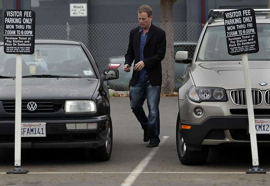 Todd Ewing returns to his car after buying a ticket to park in a lot at 17th and Folsom streets in San Francisco, Calif. on Saturday, Sept. 24, 2011. Neighborhood businesses are upset that the city has plans to convert the lot into a public park. Ewing uses the lot every Saturday to take his daughter to the ODC dance center across the street. Photo: Paul Chinn, The Chronicle