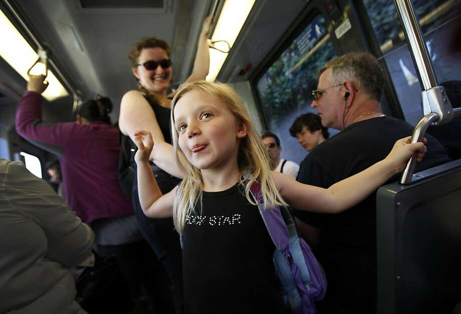 "Phaedra Powers-Miguel, 5, rides the J-Church Muni line with her mom, Krystyna Miguel (cq), in San Francisco, Calif., Tuesday, September 20, 2011.  San Francisco supervisors are proposing to let kids ride Muni for free to make San Francisco more attractive to families, but the move could cost an estimated $7 million to $9 million a year.  ""I don't see it being a practical thing right now with the economy like it is,"" Miguel said.  She said she'd love the free fare for her daughter but she doesn't think it will actually happen. Photo: Sarah Rice, Special To The Chronicle"