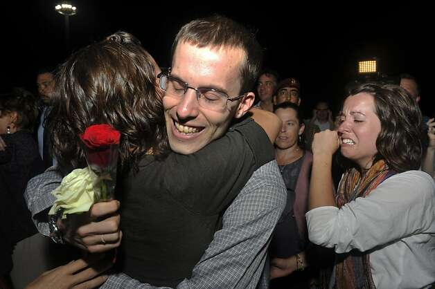 Freed American Shane Bauer, center is welcomed upon his arrival from Iran, in Muscat, Oman Wednesday, Sept. 21, 2011. After more than two years in Iranian custody, two Americans convicted as spies took their first steps toward home Wednesday as they bounded down from a private jet and into the arms of family for a joyful reunion in the Gulf state of Oman. (AP Photo/Sultan Al-Hasani) Photo: Sultan Al-Hasani, AP