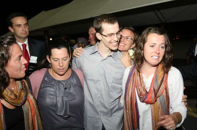 American hiker Shane Bauer (C) poses with his mother (2nd L) and two sisters and fiancee Sarah Shourd (2nd R)  after stepping off  an Omani Royal Air Force plane on September 21, 2011 in Muscat, Oman, after Tehran released Bauer and Josh Fattal on bail, months after handing them hefty jail terms.  The pair was released earlier September 21, 2011 from Tehran's notorious Evin prison, after more than two years in jail for spying and illegal entry into Iran, after the Gulf sultanate of Oman paid their bail.  Bauer and Fattal were arrested along with Shourd near the mountainous border with Iraq on July 31, 2009. All three have consistently maintained they innocently strayed into Iran while hiking in Iraq's Kurdistan region. Shourd, the third hiker, was released last year on humanitarian and medical grounds.   AFP PHOTO / Mohammed MAHJOUB (Photo credit should read MOHAMMED MAHJOUB/AFP/Getty Images) Photo: Mohammed Mahjoub, AFP/Getty Images
