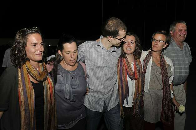 Freed American Shane Bauer, center, meets his relatives and friends upon his arrival from Iran, in Muscat, Oman Wednesday, Sept. 21, 2011. After more than two years in Iranian custody, two Americans convicted as spies took their first steps toward home Wednesday as they bounded down from a private jet and into the arms of family for a joyful reunion in the Gulf state of Oman. (AP Photo/Sultan Al-Hasani) Photo: Sultan Al-Hasani, AP