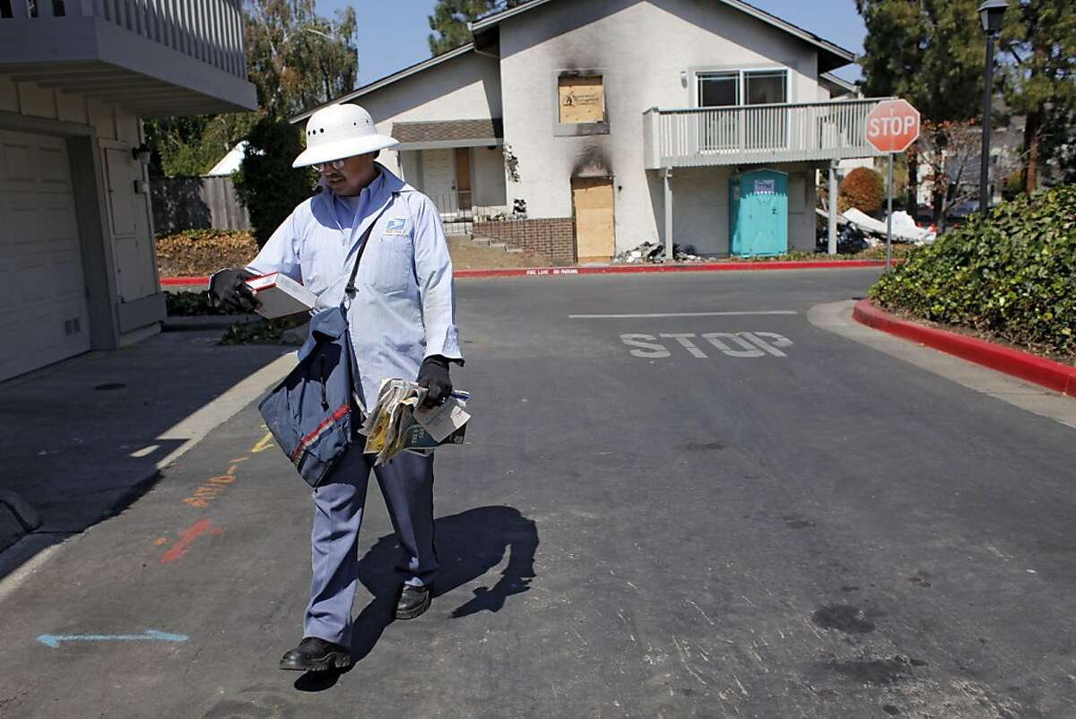Cupertino postal worker Gabriel Ortiz delivers mail to the 20289 NW Square condominium complex, Wednesday September 14, 2011, where a natural gas pipe caused an explosion and fire last month, in Cupertino, Calif.