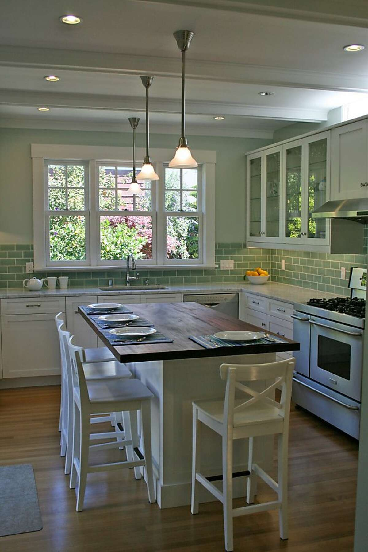 A rustic wood-covered island doubles as a place to dine in this Craftsman-style kitchen featured on the Rockridge Kitchen Tour on Oct. 2.