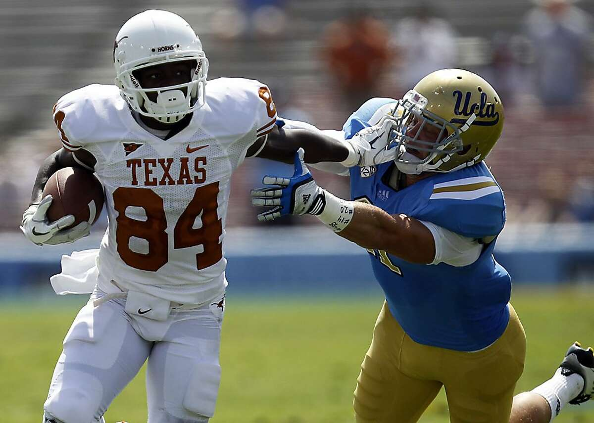 Texas wide receiver Marquise Goodwin puts a stiff arm on UCLA linebacker Sean Wsetgate in the second quarter on Saturday, September 17, 2011, at the Rose Bowl in Pasadena, California. Texas defeated UCLA, 49-20. (Luis Sinco/Los Angeles Times/MCT)