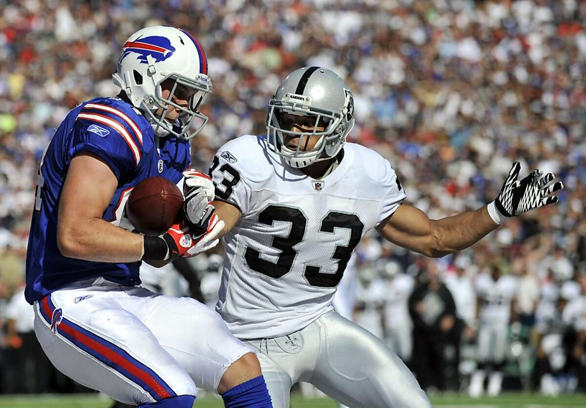 Buffalo Bills' Scott Chandler, left, makes a touchdown catch under pressure from Oakland Raiders' Tyvon Branch (33) during the second half of an NFL football game in Orchard Park, N.Y., Sunday, Sept. 18, 2011. The Bills won 38-35. (AP Photo/Gary Wiepert)