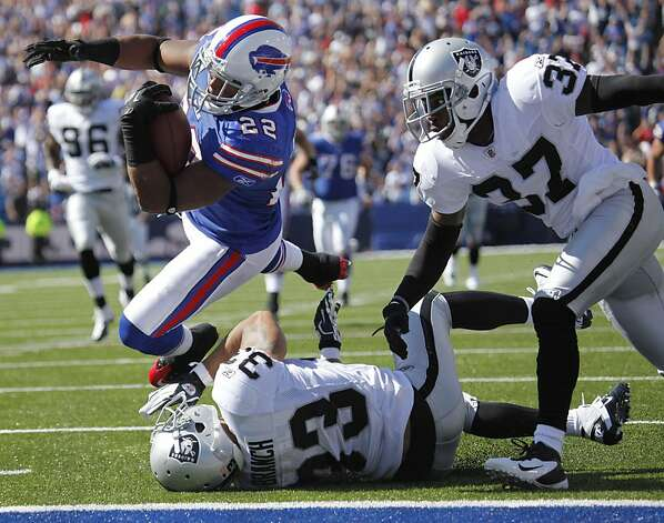 Buffalo Bills' Fred Jackson (22) leaps into the end zone for a touchdown under pressure from Oakland Raiders' Tyvon Branch (33) and Chris Johnson (37) during the third quarter of an NFL football game in Orchard Park, N.Y., Sunday, Sept. 18, 2011. (AP Photo/Derek Gee) Photo: Derek Gee, AP