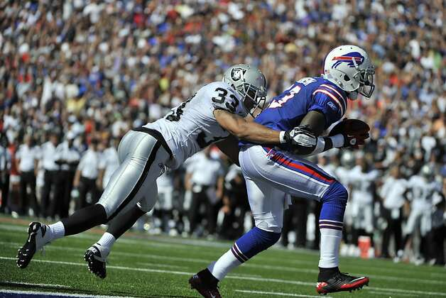 Buffalo Bills' Stevie Johnson (13) scores a touchdown under pressure from Oakland Raiders' Tyvon Branch (33) during the second half of an NFL football game in Orchard Park, N.Y., Sunday, Sept. 18, 2011. The Bills won 38-35. (AP Photo/Gary Wiepert) Photo: Gary Wiepert, AP