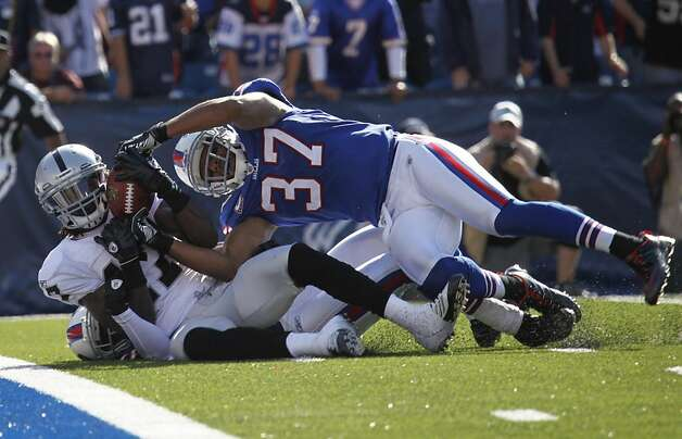 Oakland Raiders' Denarius Moore, left, catches a pass for a touchdown under pressure from Buffalo Bills' George Wilson (37) during the fourth quarter of an NFL football game in Orchard Park, N.Y., Sunday, Sept. 18, 2011. (AP Photo/Derek Gee) Photo: Derek Gee, AP