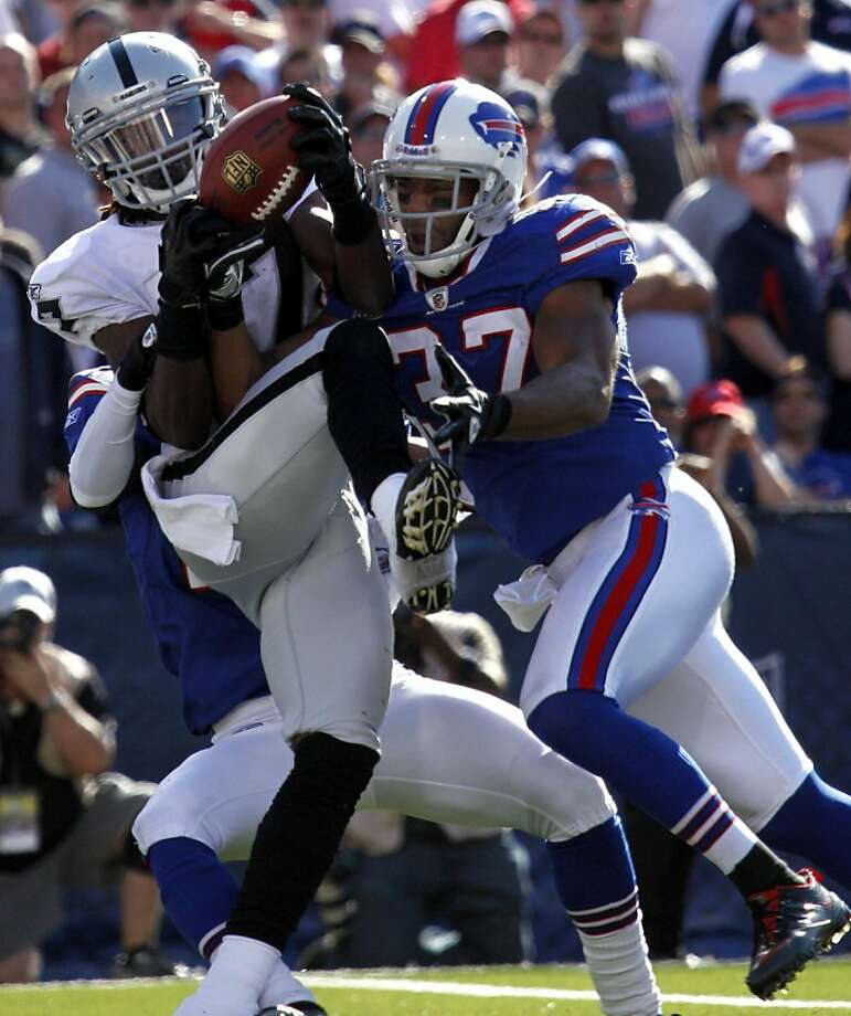 Oakland Raiders' Denarius Moore, left, catches a pass for a touchdown over Buffalo Bills' George Wilson during the fourth quarter of an NFL football game in Orchard Park, N.Y., Sunday, Sept. 18, 2011. (AP Photo/Derek Gee) Photo: Derek Gee, AP