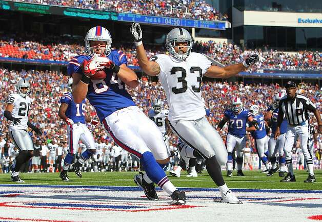 ORCHARD PARK, NY - SEPTEMBER 18: Scott Chandler #84 of the Buffalo Bills catches a touchdown pass during an NFL game as Tyvon Branch #33 of the Oakland Raiders defends at Ralph Wilson Stadium on September 18, 2011 in Orchard Park, New York. (Photo by Tom Szczerbowski/Getty Images) Photo: Tom Szczerbowski, Getty Images