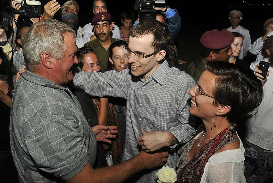 Freed American Shane Bauer, center, meets his father Al Bauer as his fiance Sarah Shourd looks on upon his arrival from Iran, in Muscat, Oman Wednesday, Sept. 21, 2011. After more than two years in Iranian custody, two Americans convicted as spies took their first steps toward home Wednesday as they bounded down from a private jet and into the arms of family for a joyful reunion in the Gulf state of Oman. (AP Photo/Sultan Al-Hasani) Photo: Sultan Al-Hasani, AP