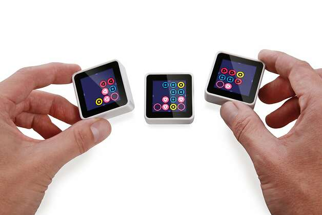 A product image of three Sifteo cubes playing one of their games, Chroma Shuffle. Photo: Sifteo