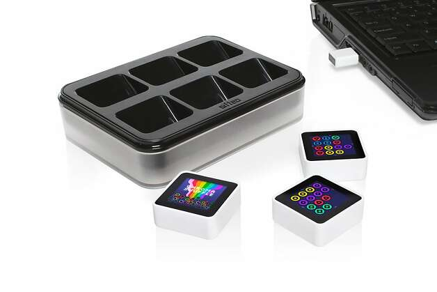 A product image of three Sifteo cubes, its charging dock and usb wireless link. The Sifteo Starter Pack sells for $149 while extra cubes are $45 each. Photo: Sifteo