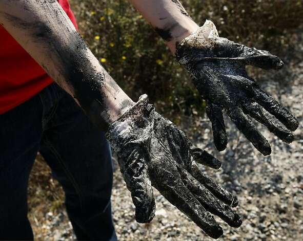 High school student Devin Harvey's gloved hands are a gooey mess after removing a decaying truck tire from the bay across from Hunter's Point in San Francisco, Calif. on  Saturday, Sept. 17, 2011. Photo: Paul Chinn, The Chronicle