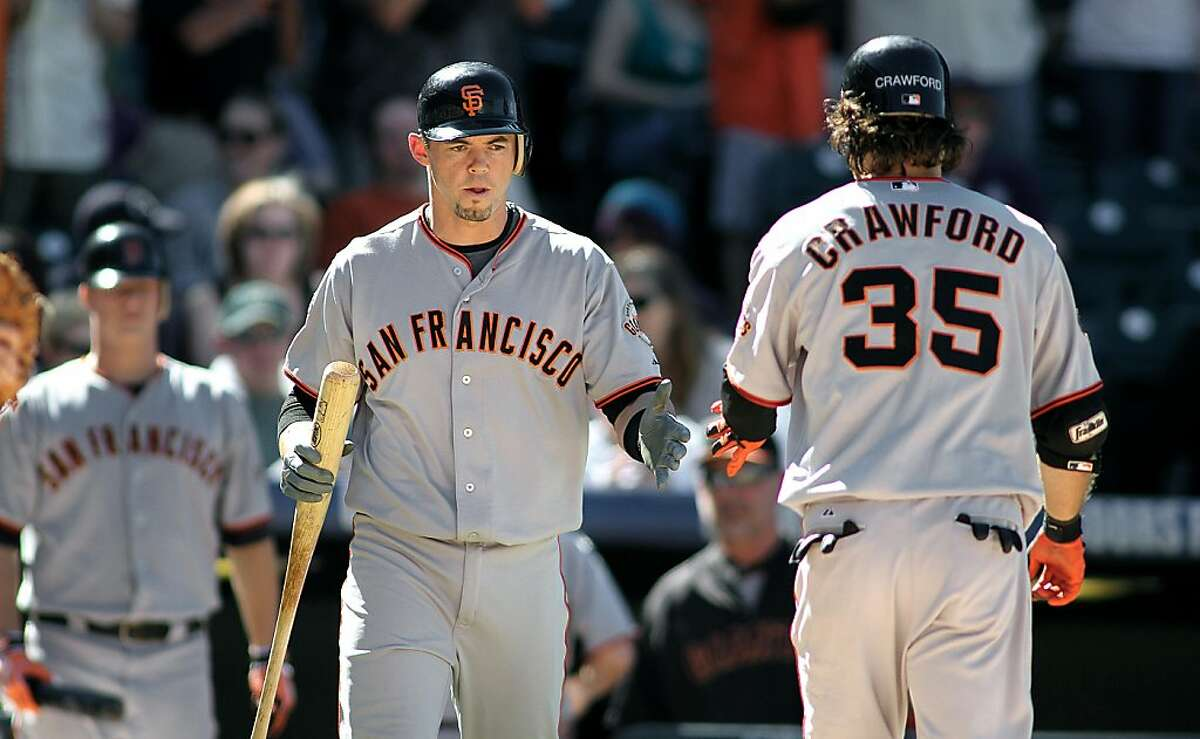 DENVER, CO - SEPTEMBER 18: Eli Whiteside #22 of the San Francisco Giants congratulates teammate Brandon Crawford #35 of the San Francisco Giants after Crawford hit a solo home run during their game at Coors Field against the Colorado Rockies on Sunday September 18, 2011 in Denver, Colorado. (Photo by Marc Piscotty/Getty Images)