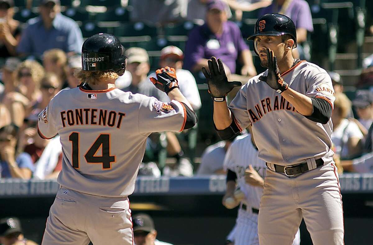 DENVER, CO - SEPTEMBER 18 : Mike Fontenot #14 of the San Francisco Giants is high-fived by teammate Andres Torres #56 of the San Francisco Giants after Fontenot hit a two run home-run in the first inning during their game at Coors Field on Sunday September 18, 2011 in Denver, Colorado. (Photo by Marc Piscotty/Getty Images)