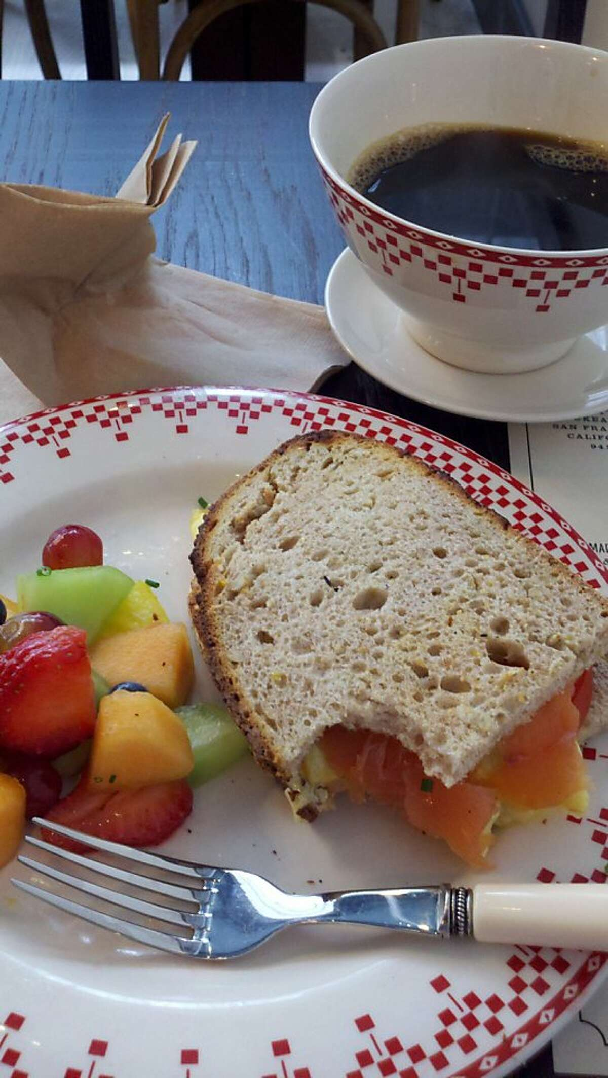 An egg and cheese sandwich with smoked salmon and a side of fruit at new La Boulange in Union Square.