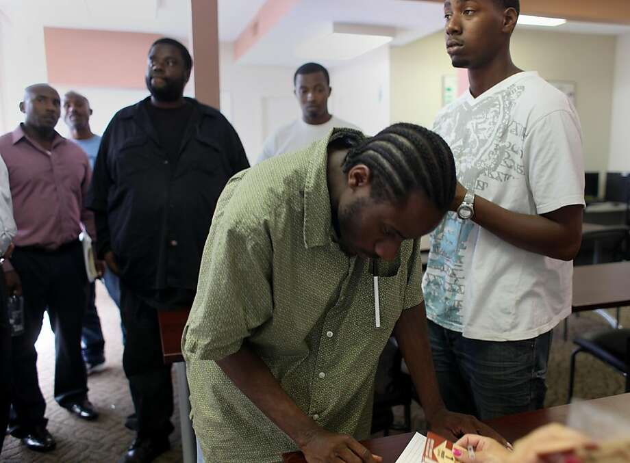 Surrounded by classmates, all looking for work, Gerald Atlas, 19, (rt) waits for a Rubicon representative to distribute free bus passes after completing a job skills workshop at Rubicon's Opportunity Center where he has been taking a crash course in finding a job on Wednesday Sept. 21, 2011 in Richmond, Calif. Atlas has been looking for a job for the past 8 months since moving here from Las Angeles. He said its a been a really frustrating process. Most of the jobs he has applied for are filled within the first day. Photo: Mike Kepka, The Chronicle