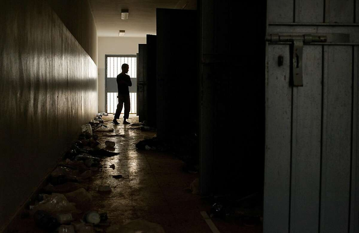 A man looks around one of the empty cell blocks at the Abu Salim prison in central Tripoli on September 19, 2011. The prison gained notoriety after over 1200 prisoners were executed there in 1996 in what became known as the