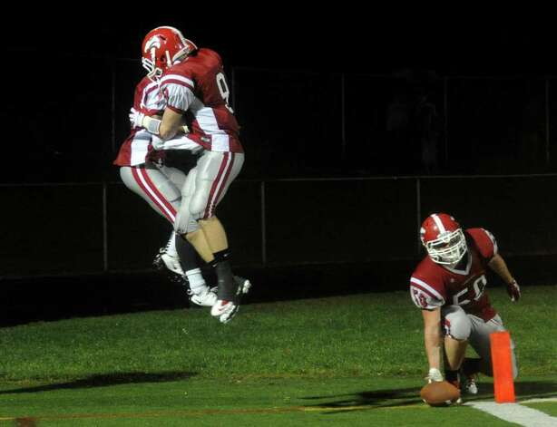 Masuk's #9 Brandon Cusmano leaps up to bump #1 Jason Piontkowski midair after Piontkowski scored a touchdown, during Class L state football playoff action against North Haven in Trumbull, Conn. on Tuesday November 29, 2011. Photo: Christian Abraham / Connecticut Post