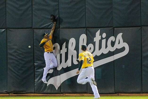 OAKLAND, CA - SEPTEMBER 16: Coco Crisp #4 of the Oakland Athletics leaps but can't catch this ball hit off the wall by Wilson Betemit #20 that drives in Jhonny Peralta #27 of the Detroit Tigers in the six inning during an MLB baseball game t O.co Coliseum on September 16, 2011 in Oakland, California.  (Photo by Thearon W. Henderson/Getty Images) Photo: Thearon W. Henderson, Getty Images