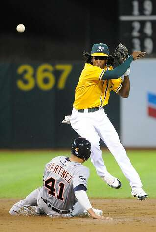 OAKLAND, CA - SEPTEMBER 16: Jemile Weeks #19 the Oakland Athletics gets his throw off to first base but can't complete the double play while avoiding the slide of Victor Martinez #41 of the Detroit Tigers during an MLB baseball game at O.co Coliseum on September 16, 2011 in Oakland, California.  (Photo by Thearon W. Henderson/Getty Images) Photo: Thearon W. Henderson, Getty Images