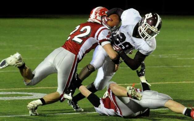 Masuk's #22 Thomas Milone, left, and teammate #10 Shawn Flynn, tackle North Haven's #29Untereance Thomas, during Class L state football playoff action in Trumbull, Conn. on Tuesday November 29, 2011. Photo: Christian Abraham / Connecticut Post