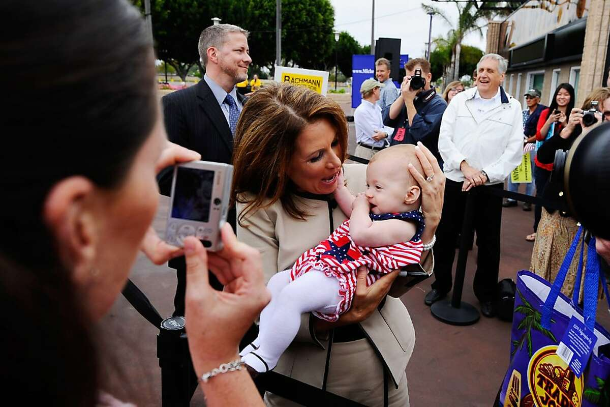 COSTA MESA, CA - SEPTEMBER 16: Republican presidential candidate Rep. Michele Bachmann (R-MN) holds Jane Morrissey, 6 months, from Tustin, California, as her mother Heather Morrissey (L) takes a picture of them during a rally at the Orange County Fairgrounds on September 16, 2011 in Costa Mesa, California. Bachmann will appear on