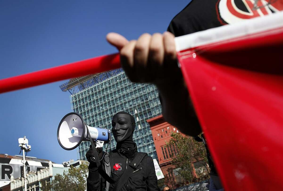 An anonymous protestor leads a chant during a BART protest at the Civic Center station in San Francisco, Calif., Monday, August 29, 2011.